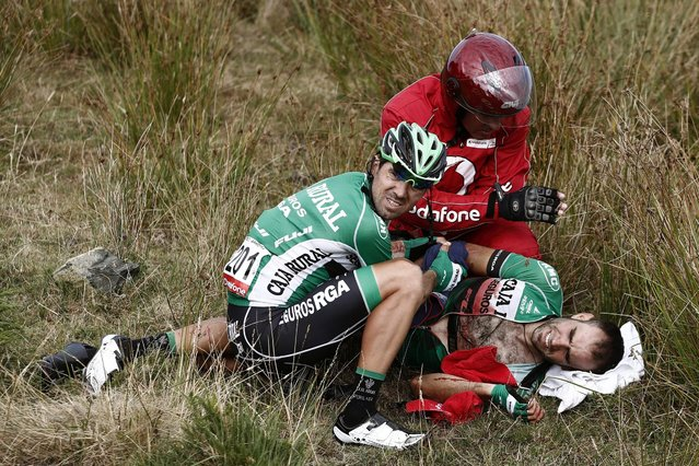 Spanish rider Lluis Mas (R) of Caja Rural team receives treatment after falling at the end of the fourth stage of La Vuelta cycling tour between Betanzos and San Andres de Teixido, in Galicia, Spain, 23 August 2016. The stage covered 163.5 km. (Photo by Javier Lizon/EPA)