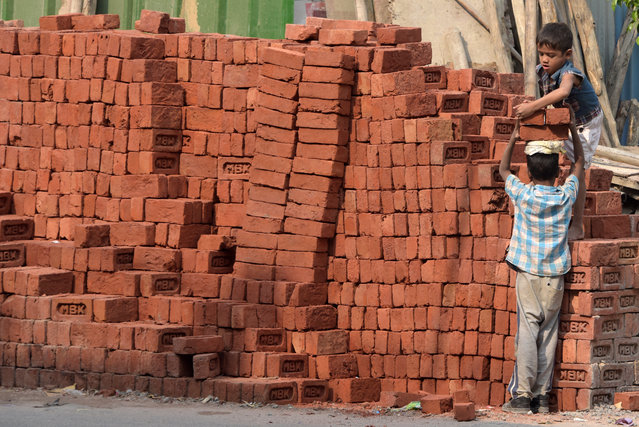 This photograph taken on November 19, 2017 shows children loading bricks at a building site in New Delhi. (Photo by Dominique Faget/AFP Photo)