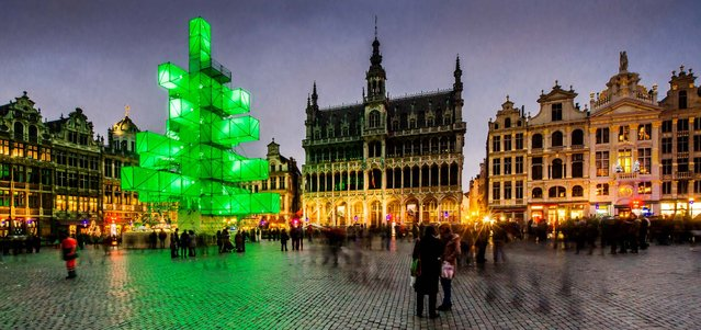 An abstract light installation replaces the traditional Christmas tree at the Grand Place in Brussels. Traditionally, a 65 ft. pine tree from the forests of the Ardennes decorates the city's central square, the Grand Place. This year, it has been replaced with an 82 ft. construction. (Photo by Geert Vanden Wijngaert/Associated Press)
