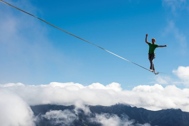 "Samuel Metzger  a professional mountaineer, balances on the ""highline"" during the European Highline Meeting on the top of the Moleson mountain at 2000 meters above the sea level, in the Swiss Alps, near Fribourg, Switzerland, Friday, October 17, 2014. Balancing on the ""slackline"" is a popular training method for climbers to improve their equilibrium sense. Other than balancing on the ""slackline"" which is in a low distance to the ground, balancing on the ""highline"" is a more extreme thrill, because it is done in dangerous altitudes. (Photo by Jean-Christophe Bott/AP Photo/Keystone)"