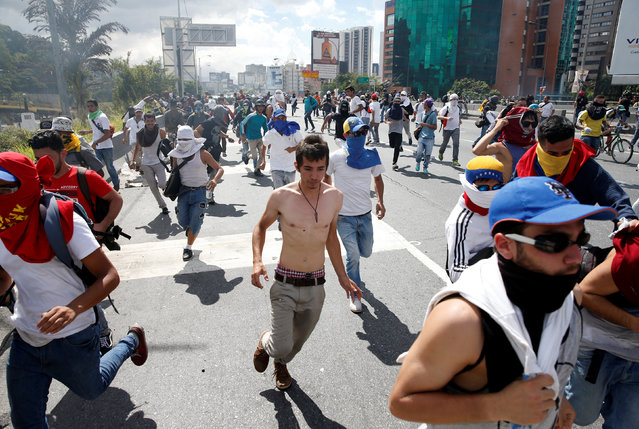 Protesters run after clashes with the police during a rally to demand a referendum to remove Venezuela's President Nicolas Maduro in Caracas, Venezuela, September 1, 2016. (Photo by Carlos Garcia Rawlins/Reuters)