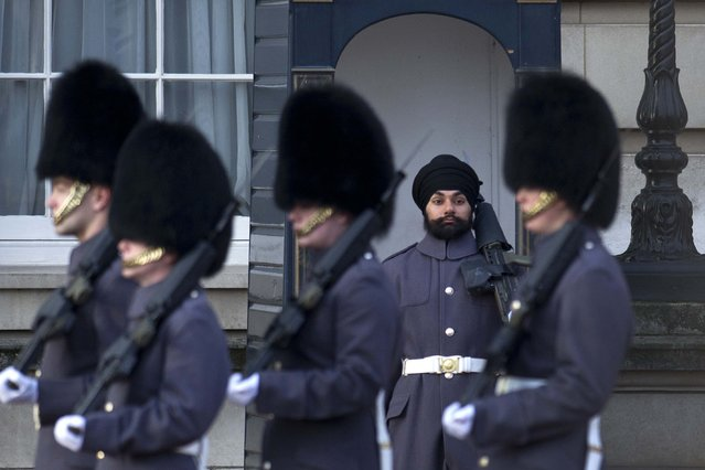 Sikh Scots Guards soldier Jatenderpal Singh Bhullar (2-R), stands on guard duty outside Buckingham Palace in central London on December 13, 2012. Jatenderpal Singh Bhullar became the first guardsman to parade outside Buckingham Palace wearing a turban instead of the bearskin. (Photo by Carl Court)