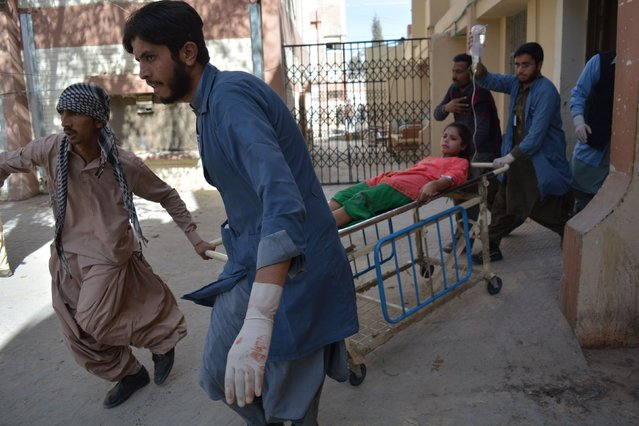 Relatives shift an injured victim after suicide bombers attacked a Methodist church during a Sunday service in Quetta on December 17 2017. (Photo by Banaras Khan/AFP Photo)