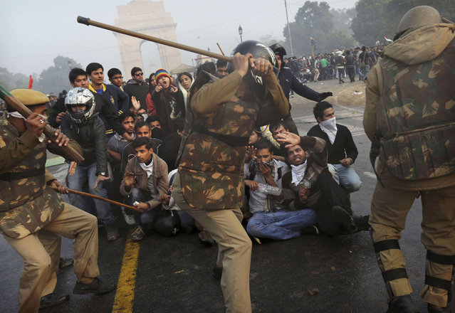 Protesters shield themselves as Indian police prepare to beat them during a violent demonstration near the India Gate, on December 23, 2012. (Photo by Kevin Frayer/AP Photo)