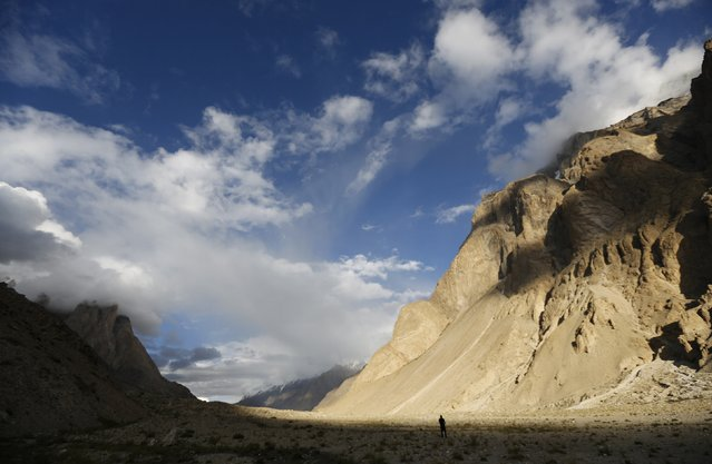 A trekker stands in the valley of the Braldu River at Bardoumal along the K2 base camp trek in the Karakoram mountain range in Pakistan August 29, 2014. (Photo by Wolfgang Rattay/Reuters)