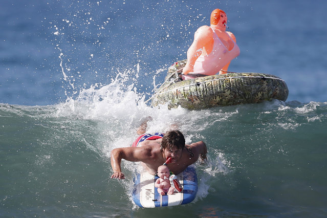 """John Broz, 28, rides a wave in a costume entitled """"The redneck yacht club"""" during the 7th annual ZJ Boarding House Haunted Heats Halloween surf contest. (Photo by Lucy Nicholson/Reuters)"""