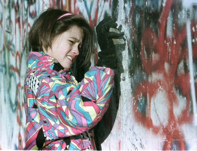 A young West German girl hammer the Berlin Wall, November 19, 1989. (Photo by Reuters)