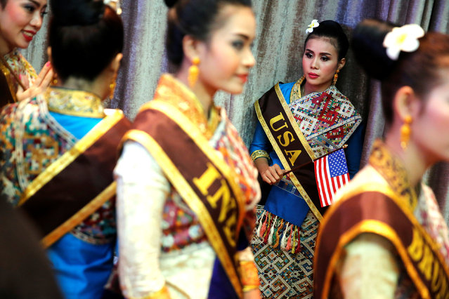 A woman in a USA sash, who would help show U.S. President Barack Obama to his seat, waits with other women in traditional dress for the start of the ASEAN Summit gala dinner in Vientiane, Laos September 7, 2016. (Photo by Jonathan Ernst/Reuters)