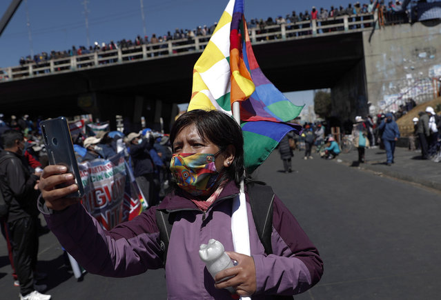 A woman wearing a mask amid the COVID-19 pandemic takes a photo with her cell phone during a protest against the postponement of the presidential election in El Alto, Bolivia, Thursday, August 13, 2020. Citing the ongoing new coronavirus pandemic, Bolivia's highest electoral authority delayed presidential elections from Sept. 6 to Oct. 18, the third time the vote has been delayed. (Photo by Juan Karita/AP Photo)