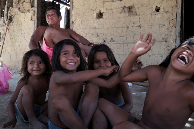 "Lourenzo Guajajara, 60, chief of the village of Bom Jardim, surrounded by children in Araribóia Indigenous Reserve, Maranhão, Brazil on August 8, 2015. Guajajara said that the Guardians of the Forest  had increased tensions in the area. ""It is bringing problems to us"". Loggers have been stealing hardwood trees from indigenous lands in Brazil. The Guardians of the Forest are an armed militia formed by the Guajajara tribe to protect their reserve. (Photo by Bonnie Jo Mount/The Washington Post)"
