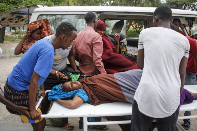 Medical workers and other Somalis help a civilian woman, who was wounded when a powerful car bomb blew off the security gates to the Elite Hotel, as she arrives at a hospital in Mogadishu, Somalia Sunday, August 16, 2020. A Somali police officer says at least 10 people have been killed and more than a dozen others injured in an ongoing siege at the beachside hotel in Somalia's capital where security forces are battling Islamic extremist gunmen who have invaded the building. (Photo by Farah Abdi Warsameh/AP Photo)