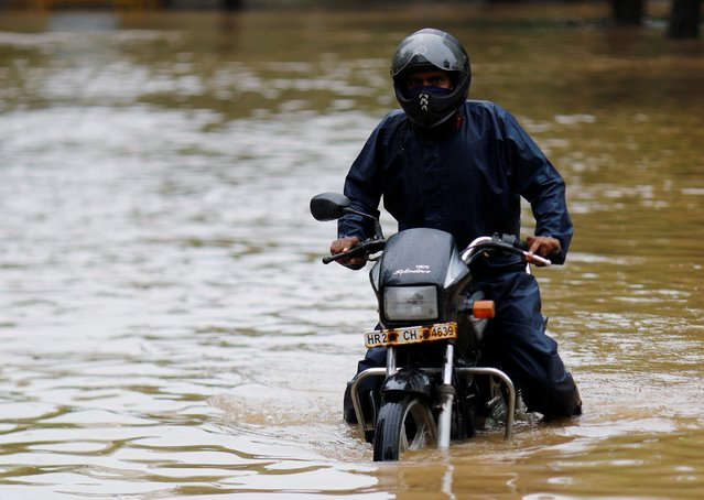 A man got stuck on his bike in a flooded street after heavy rains in Gurugram, India, August 20, 2020. (Photo by Adnan Abidi/Reuters)