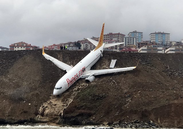 A Pegasus airplane is seen stuck in mud as it skidded off the runway after landing in Trabzon Airport, Turkey early Sunday on January 14, 2018. A passage plane which belongs to Turkey' s Pegasus Airlines skidded off the runway of Trabzon airport Saturday and ended up halfway down a steep slope into the Black Sea, Turkish media reported on Sunday. 162 passengers and crew on board were safely evacuated. (Photo by Hakan Burak Altunoz/Anadolu Agency/Getty Images)