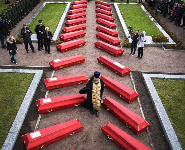 An Orthodox priest conducts a reburial ceremony of remains of Soviet soldiers killed during World War II, discovered by members of volunteer search teams in a memorial cemetery at Nevsky Pyatachok near Kirovsk, Russia, Friday, Sept. 16, 2016. Nevsky Pyatachok, an area about 50 kilometers (30 miles) southeast of St. Petersburg, has proved especially fertile ground. As many as 200,000 Soviet soldiers were killed here between September 1941 and May 1943 in fighting to break the Nazi siege of the city, which was then called Leningrad. The remains of 264 were buried Friday. (AP Photo/Dmitri Lovetsky) ORG XMIT: XDL101