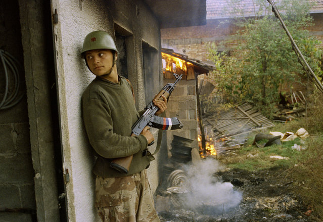 A Serbian soldier takes cover by a burning house in the village of Gorica, Bosnia-Herzegovina Sunday, October 12, 1992. The Serbs are fighting to reopen a land corridor linking the Krajina region of Northern Bosnia with Serbia. (Photo by Matija Kokovic/AP Photo)