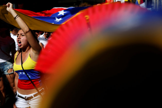 Protesters hold a Venezuelan flag during a demonstration to demand a referendum to remove Venezuela's President Nicolas Maduro, in Madrid, Spain, September 4, 2016. (Photo by Susana Vera/Reuters)
