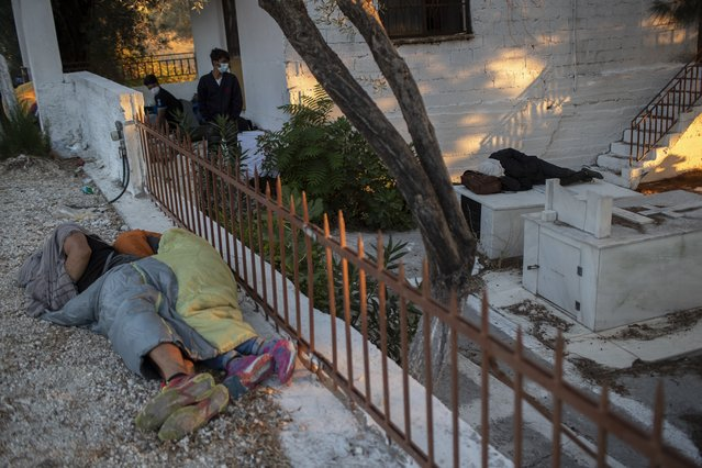 Migrants sleep at a cemetery near the Moria refugee camp on the northeastern island of Lesbos, Greece, Thursday, September 10, 2020. A second fire in Greece's notoriously overcrowded Moria refugee camp destroyed nearly everything that had been spared in the original blaze, Greece's migration ministry said Thursday, leaving thousands more people in need of emergency housing. (Photo by Petros Giannakouris/AP Photo)