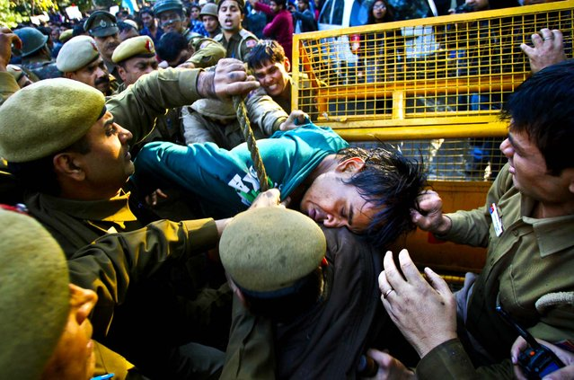 Police detain a protester during a demonstration by students against Gujarat chief minister Narendra Modi, outside the Shri Ram College of Commerce in New Delhi, India, on February 6, 2013. (Photo by Tsering Topgyal/Associated Press)