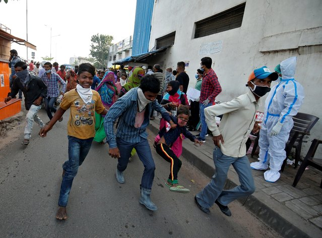 A daily wage migrant labourer runs with his son as he and other labourers are chased away by police who according to the police had gathered for day work and were not following COVID-19 social distancing in Ahmedabad, India, September 11, 2020. (Photo by Amit Dave/Reuters)