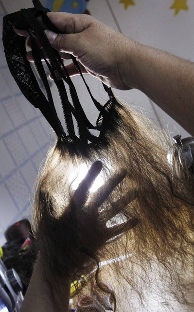 Marcela Reyes holds up a natural hair wig she is making to be donated to a girl undergoing chemotherapy for cancer, in Santiago, August 22, 2014. (Photo by Rodrigo Garrido/Reuters)