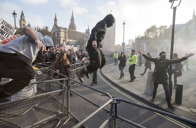 Demonstrators break through barricades in Parliament Square in front of the Houses of Parliament, as they participate in a protest against student loans and in favour of free education, in central London November 19, 2014. (Photo by Peter Nicholls/Reuters)