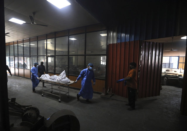 Workers push a stretcher carrying the body of a COVID-19 victim for cremation in New Delhi, India, Wednesday, September 16, 2020. India is now second in the world with the number of reported coronavirus infections with over 5.1 million cases, behind only the United States. Its death toll of only 83,000 in a country of 1.3 billion people, however, is raising questions about the way it counts fatalities from COVID-19. (Photo by Manish Swarup/AP Photo)