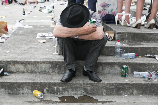 A drunk man rests his head whilst holding his beer can during the Emirates Melbourne Cup Day held at Flemington Racecourse in Melbourne Australia, on November 4, 2014. (Photo by Asanka Brendon/Rex Features)