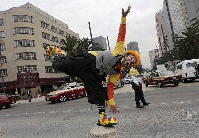 A clown performs next to the Monument to the Revolution as he takes part in the Latin American Clown Convention in Mexico City, Mexico, October 21, 2015. (Photo by Henry Romero/Reuters)