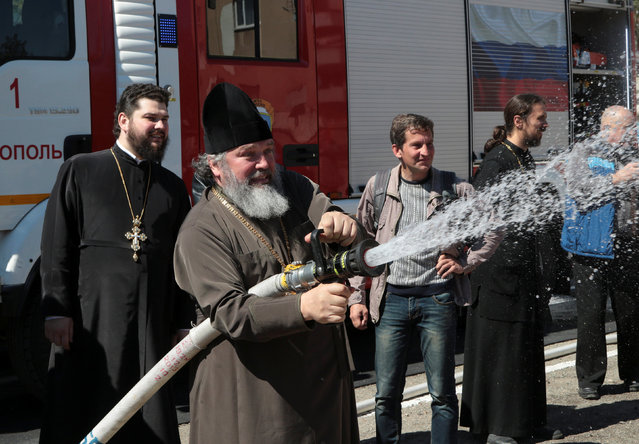 An Orthodox priest takes part in practical exercises on fire extinguishing in Simferopol, Crimea, April 4, 2017. (Photo by Pavel Rebrov/Reuters)
