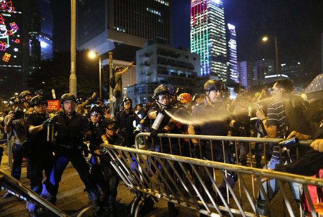 A policeman uses pepper spray while clashing with pro-democracy protesters close to the chief executive office in Hong Kong, November 30, 2014. (Photo by Tyrone Siu/Reuters)
