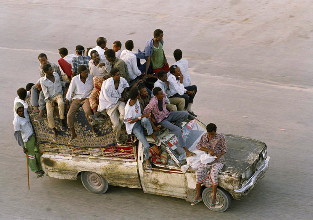 A decrepit taxi sags under the weight of far too many passengers in Mogadishu, January 19, 1993. The price of a ride inside the taxi through the devastated capital of Somalia is twenty U.S. cents and half that for a ride on the roof of the taxi, or hanging off the back. (Photo by Greg Marinovich/AP Photo)