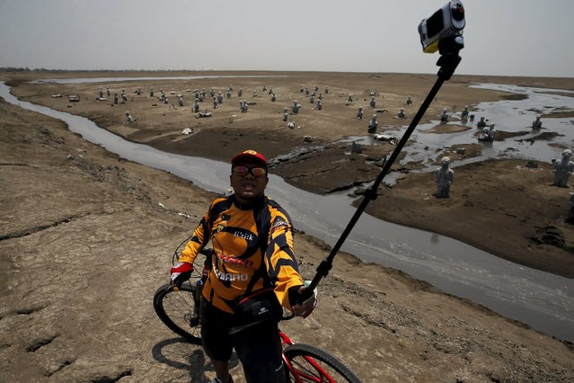 A cyclist takes a picture of himself at the Lapindo mud field in Sidoarjo, October 11, 2015. (Photo by Reuters/Beawiharta)