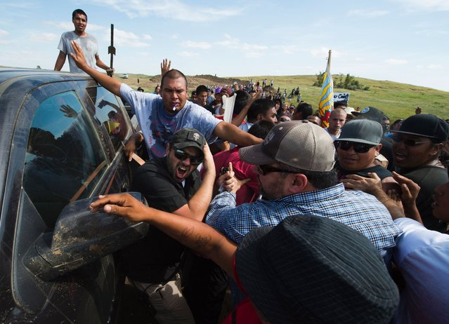 Native American protestors and their supporters are confronted by security during a demonstration against work being done for the Dakota Access Pipeline near Cannonball, North Dakota, September 3, 2016. (Photo by Robyn Beck/AFP Photo)