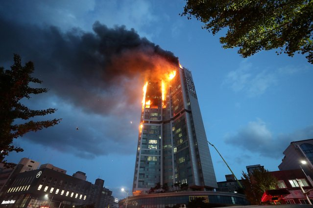 Flames and smoke rise from a fire at an apartment building in Ulsan on October 9, 2020. The Yonhap news agency reported that firefighters were struggling to put out the fire for more than nine hours, and that at least 88 people were sent to hospitals for smoke inhalation. (Photo by Yonhap/AFP Photo/Stringer)