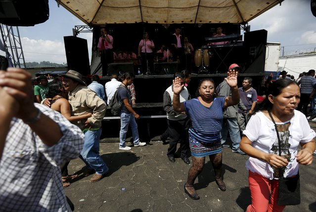 People dance outside of the church in honor of San Simon in Iztapa, in Chimaltenango, around 62 km (39 miles), from Guatemala City, October 28, 2015. (Photo by Jorge Dan Lopez/Reuters)