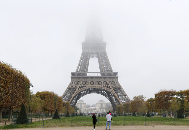 Fog and smog swallow up the top of the Eiffel Tower in Paris. Monday, November 2, 2015. Paris authorities have put in place measures to limit traffic after high levels of pollution in the French capital. France is proposing the automatic updating of countries' emissions targets in a climate deal to be thrashed out at a U.N. conference in Paris beginning later this month. (Photo by Jacques Brinon/AP Photo)