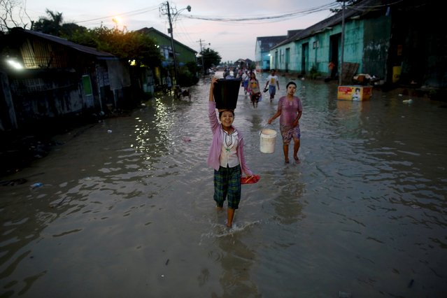 A girl carries a basket on her head as she walks along a flooded street in Yangon in this September 30, 2015 file photo. (Photo by Soe Zeya Tun/Reuters)
