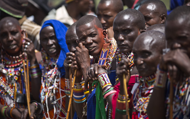 A group of Maasai women watch the high jump at the annual Maasai Olympics in the Sidai Oleng Wildlife Sanctuary near to Mt. Kilimanjaro, in southern Kenya, Saturday, December 13, 2014. (Photo by Ben Curtis/AP Photo)