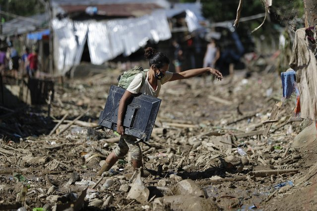 A woman carries a computer monitor she retrieved from her house at the typhoon-damaged Kasiglahan village in Rodriguez, Rizal province, Philippines, Friday, November 13, 2020. Thick mud and debris coated many villages around the Philippine capital Friday after Typhoon Vamco caused extensive flooding that sent residents fleeing to their roofs and killing dozens of people. (Photo by Aaron Favila/AP Photo)