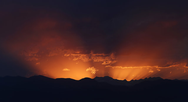 The setting sun lights the evening sky behind the mountains west of Denver late Thursday, June 29, 2017. Forecasters predict that the warm weather will relent on Friday before the heat returns over the Fourth of July holiday, sending temperatures into the mid-90s. (Photo by David Zalubowski/AP Photo)