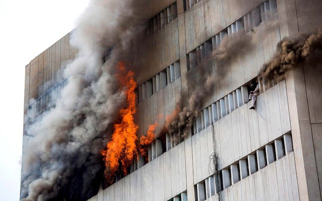 As a fire burns at the Lahore Development Authority Plaza, a man is perched at a window moments before being overcome by fumes and falling out of the window. Rescue work is underway at the site of the fire as helicopters are used to save stranded victims from the roof of the building. (Photo by Daniel Berehulak/Getty Images)