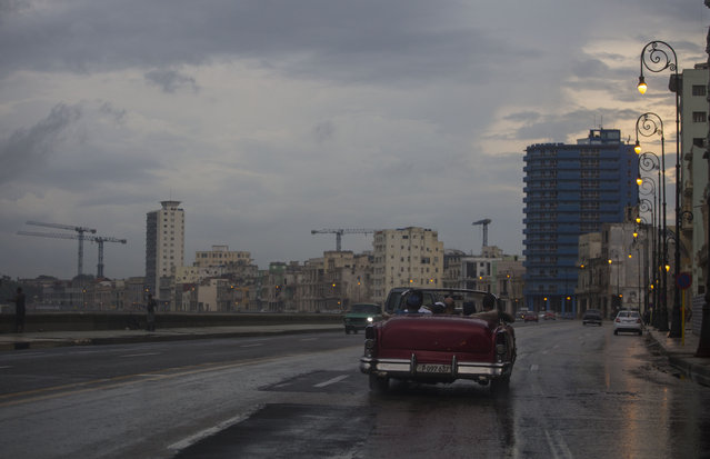 In this October 12, 2017 photo, a vintage car carries tourists for a spin on the Malecon in Havana, Cuba. Havana starts on the Malecon, the elegant, crumbling coastal boulevard whose early 20th-century buildings face a sea that sprays them with salt and pounds them with massive waves brought in by cold fronts or hurricanes. (Photo by Desmond Boylan/AP Photo)