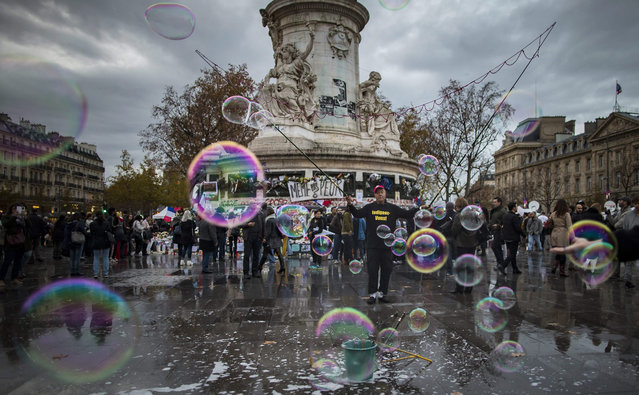 A man makes bubbles using string and soapy water on Place de la Republique, where crowds gather daily to pay tribute to the victims of the 13 November attacks in Paris, France, 19 November 2015. aris suffered terrorist attacks at the hands of the so-called Islamic State on November 13, when Islamist suicide bombers and gunmen claimed the lives of 129 people, and injured 352. (Photo by Ian Langsdon/EPA)