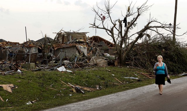 A woman walks near a destroyed home in Moore. (Photo by Steve Sisney/The Oklahoman)