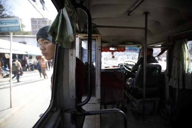 Suraj Shrestha, the conductor of a women-only bus, stands at the bus door as he waits for women passengers at the bus stand in Kathmandu January 6, 2015. (Photo by Navesh Chitrakar/Reuters)