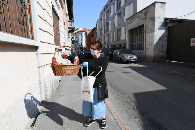 A woman puts groceries into a basket where people can donate or take free food, amid the coronavirus disease (COVID-19) outbreak in Milan, Italy on April 9, 2020. (Photo by Daniele Mascolo/Reuters)