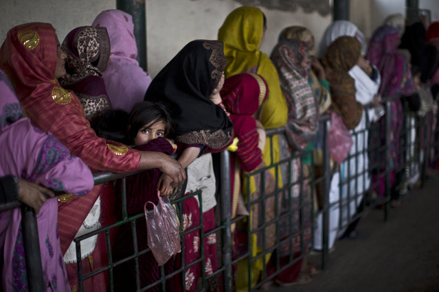 Pakistani women and children wait their turn to receive rice during a donated food distribution on the occasion of Prophet Muhammad's birthday at a shrine in Islamabad, Pakistan, Sunday, January 4, 2015. (Photo by Muhammed Muheisen/AP Photo)