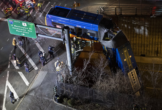 A bus in New York City which careened off a road in the Bronx neighborhood of New York is left dangling from an overpass Friday, January. 15, 2021, after a crash late Thursday that left the driver in serious condition, police said. (Photo by Craig Ruttle/AP Photo)