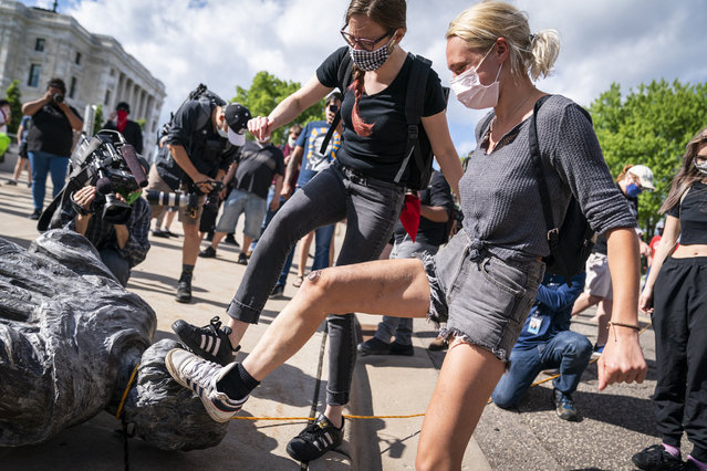 People take turns stomping the Christopher Columbus statue after it was toppled in front of the Minnesota State Capitol in St. Paul, Minn., on Wednesday, June 10, 2020. (Photo by Leila Navidi/Star Tribune via AP Photo)