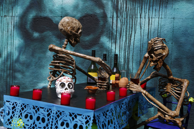 Skeletons are arranged in a bar scene as part of a competition to create Day of the Dead altars on pedestrian Regina Street in central Mexico City, Tuesday, November 1, 2016. The holiday honors the dead as friends and families gather in cemeteries to decorate their loved ones' graves and hold vigil through the night on Nov. 1 and 2. (Photo by Rebecca Blackwell/AP Photo)